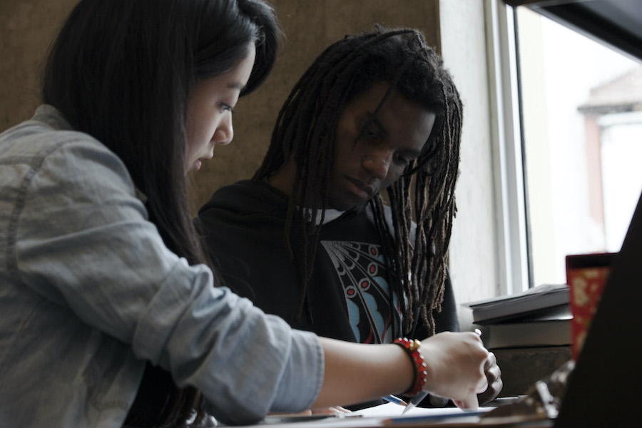 Two people sitting at a desk looking at a piece of paper between them